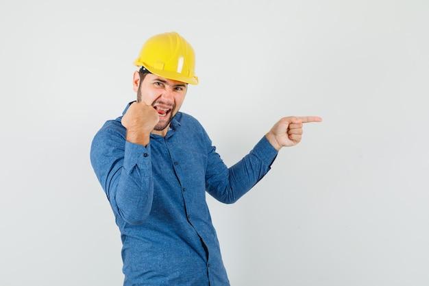 Молодой рабочий, указывая в сторону, показывая жест победителя в рубашке, шлеме и блаженный.