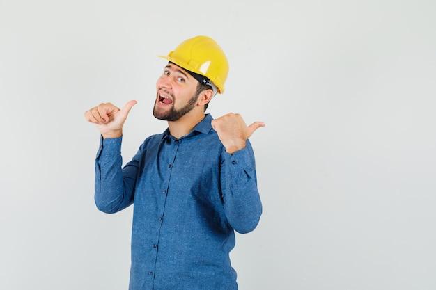 シャツ、ヘルメット、幸せそうに見える親指で横を指している若い労働者