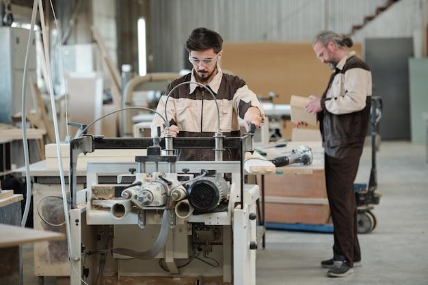 그의 수석 동료 또는 마스터가 나무 보드를 선택하는 동안 산업 기계에서 젊은 작업자 가공 공작물