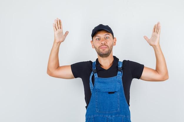 유니폼, 전면보기에 팔과 손을 올리는 젊은 노동자.