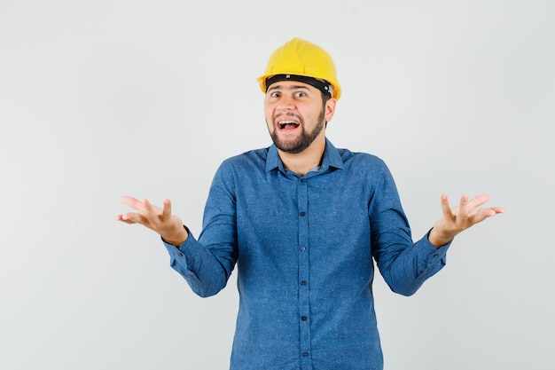 Young worker raising hands in questioning manner in shirt, helmet