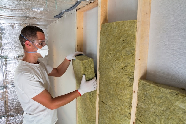 Young worker in respirator insulating rock wool insulation staff in wooden frame for future house walls for cold barrier. comfortable warm home, economy, construction and renovation concept.