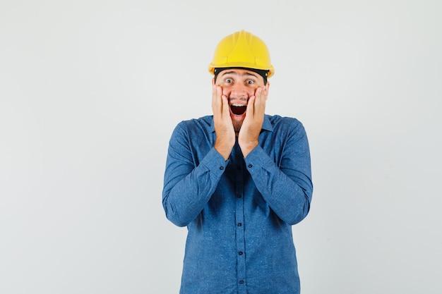 Giovane operaio in camicia, casco tenendosi per mano sulle guance e guardando stupito
