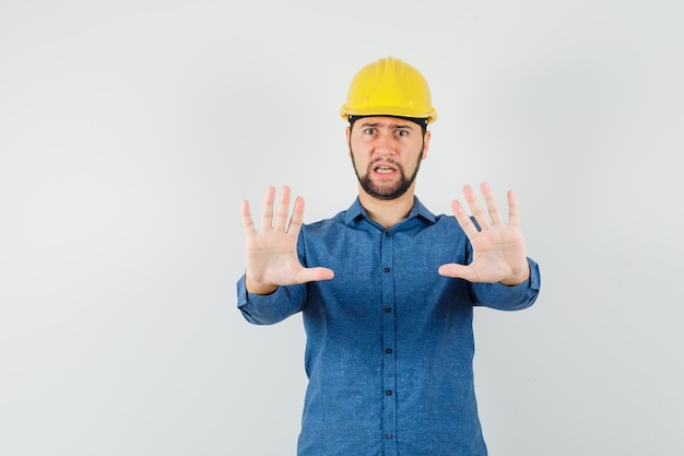 Giovane operaio in camicia, casco che mostra il gesto di rifiuto e che sembra irritato