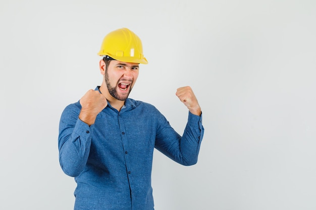 Young worker in shirt, helmet showing winner gesture and looking happy
