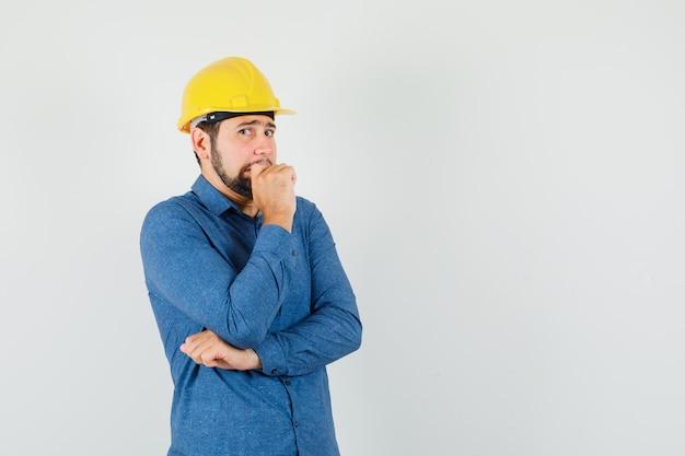 Giovane operaio in camicia, casco in piedi nella posa di pensiero e che sembra spaventato
