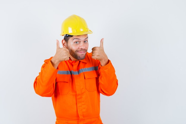 Young worker showing double thumbs up in uniform, helmet and looking positive.
