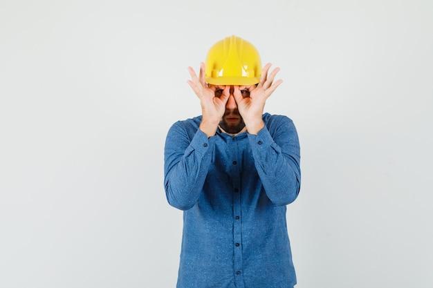 젊은 노동자 셔츠, 헬멧에 안경 제스처를 보여주는 초점을 찾고