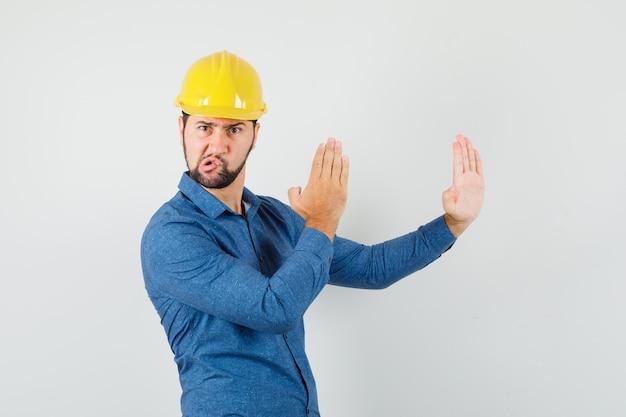 Giovane operaio che mostra il gesto di taglio di karate in camicia, casco e che sembra arrabbiato.