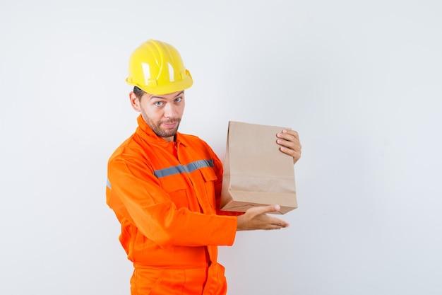 制服を着た紙袋を示す若い労働者