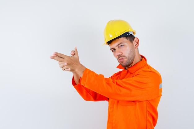 젊은 노동자 유니폼, 헬멧에 촬영 제스처를 보여주는 자신감을 찾고.
