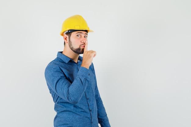 Молодой работник показывает жест молчания в рубашке, шлеме и смотрит осторожно.
