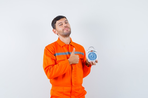 Young worker showing thumb up, holding alarm clock in uniform and looking confident.