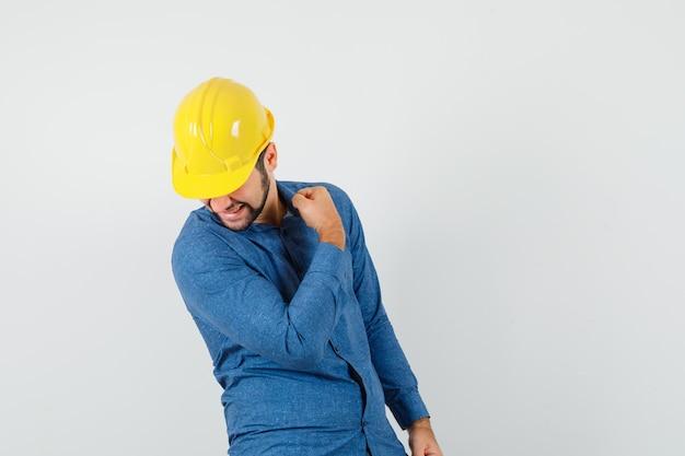 Giovane operaio che mostra il gesto del vincitore in camicia, casco e che sembra felice