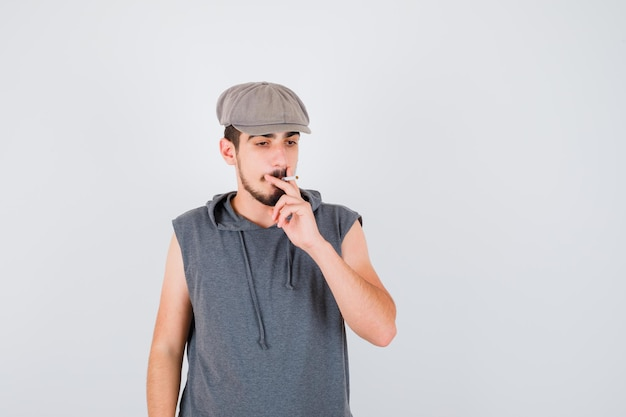 Young worker smoking cigarette and holding it in gray t-shirt and cap and looking serious