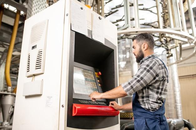 生産ラインのコントロールパネルのそばに立って、ディスプレイ上の処理の設定を選択する若年労働者