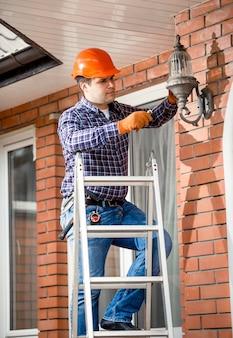 Молодой работник стоит на высокой лестнице и меняет лампочку на уличный фонарь