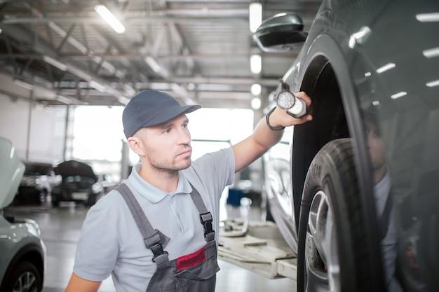 若年労働者は車の近くに立って、ライトを保持します。彼は真面目で集中しています。