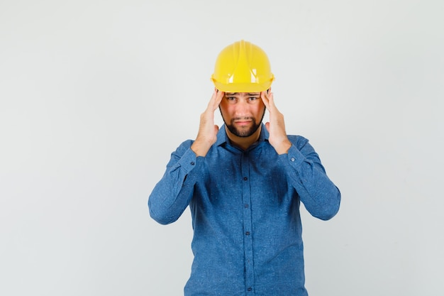 Young worker suffering from strong headache in shirt, helmet and looking tired