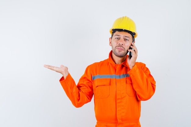 Young worker talking on mobile phone, spreading palm aside in uniform, helmet.