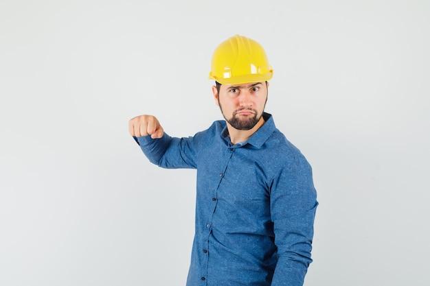 젊은 노동자 셔츠, 헬멧에 주먹으로 위협하고 긴장을 찾고