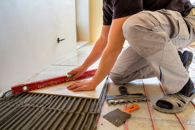 Young worker tiler installing ceramic tiles using lever on cement floor with heating red electrical cable wire system
