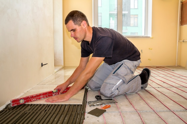 Young worker tiler installing ceramic tiles using lever on cement floor with heating red electrical cable wire system.