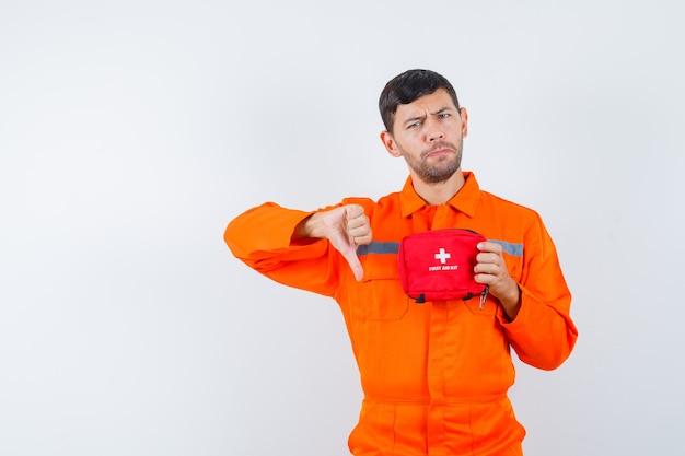 Giovane operaio in uniforme che tiene il kit di pronto soccorso, mostrando il pollice verso il basso e guardando insoddisfatto.