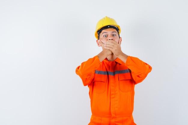 Giovane operaio in uniforme che tiene le mani sulla bocca e sembra spaventato.