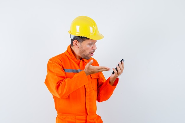 Giovane operaio in uniforme guardando il telefono cellulare e guardando arrabbiato.
