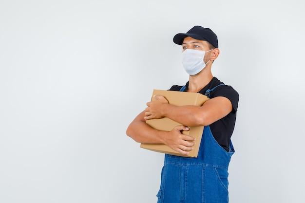 Giovane operaio in uniforme, maschera tenendo la scatola di cartone e guardando lontano, vista frontale.