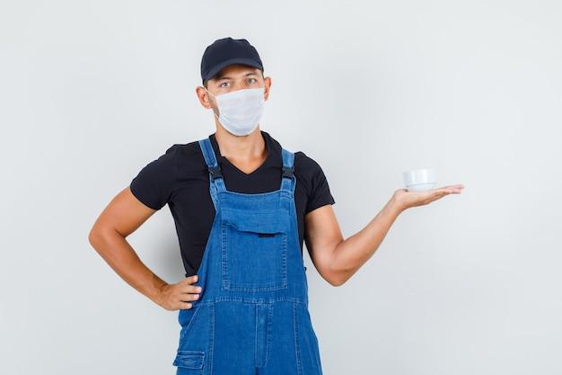 Giovane operaio in uniforme, maschera che tiene tazza con la mano sulla vita, vista frontale.