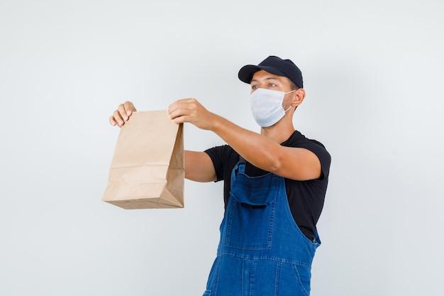 Giovane operaio in uniforme, maschera che tiene il sacchetto di carta, vista frontale.