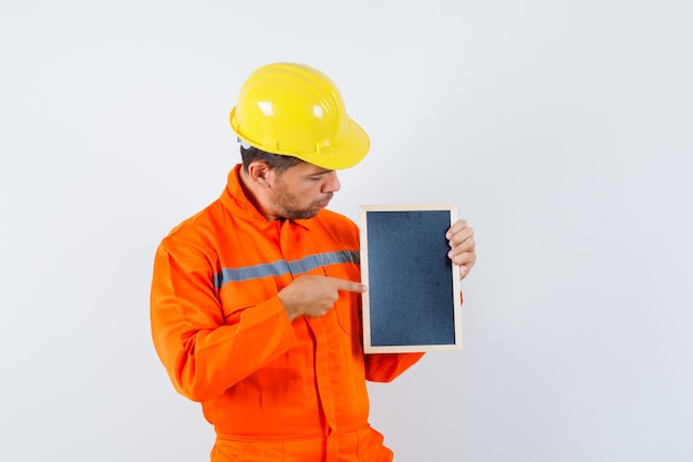Giovane operaio in uniforme che indica alla lavagna e che sembra concentrato.