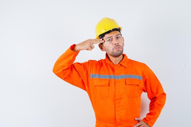 Giovane operaio in uniforme che indica la mano e le dita alla testa.