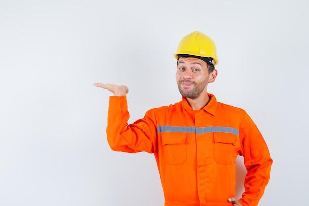 Giovane operaio in uniforme che alza il palmo come tenere o mostrare qualcosa e guardando felice.