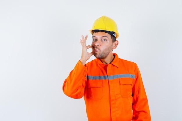 Giovane operaio in uniforme che mostra il gesto della chiusura lampo e che osserva attento.