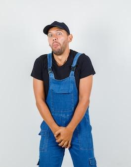 Молодой работник хочет в туалет, держа его за промежность в форме спереди.