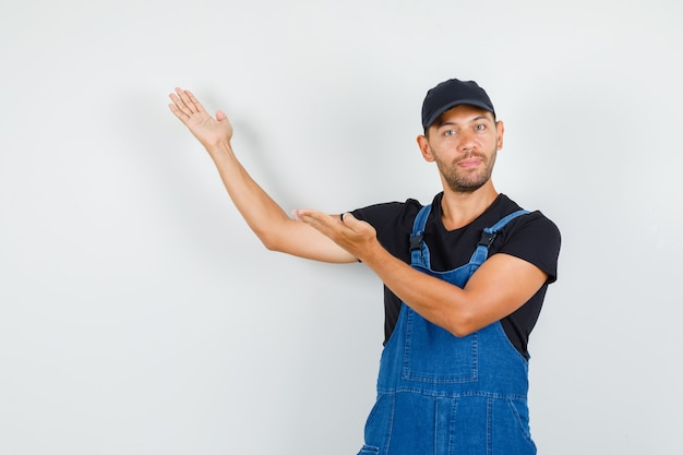 Молодой рабочий приветствует или показывает что-то с открытыми ладонями в униформе, вид спереди.