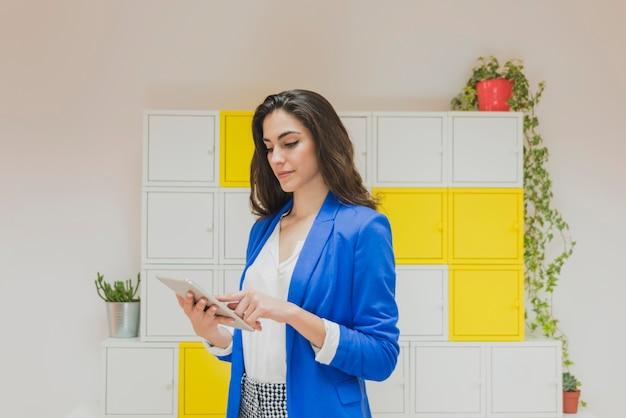 Giovane operaio con la giacca blu che controlla il suo tablet in ufficio
