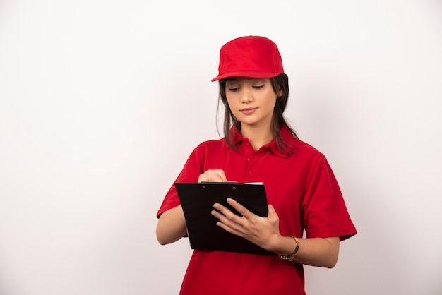 Giovane operaio con uniforme rossa e appunti su sfondo bianco.