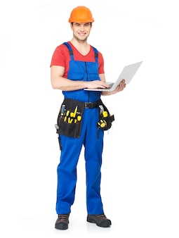 Young worker with tools holds the laptop full portrait on white