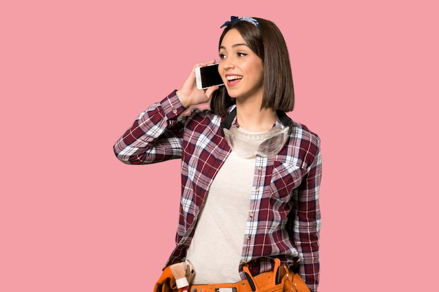 Young worker woman keeping a conversation with the mobile phone on isolated pink wall