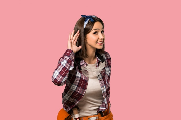 Young worker woman listening to something by putting hand on the ear on isolated pink wall