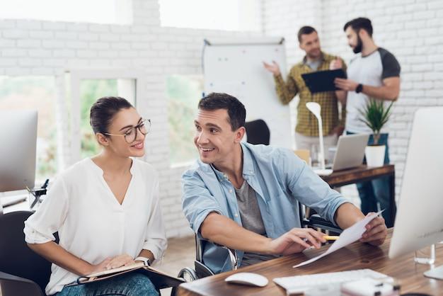 若い労働者は近代的なオフィスで会話をしています。