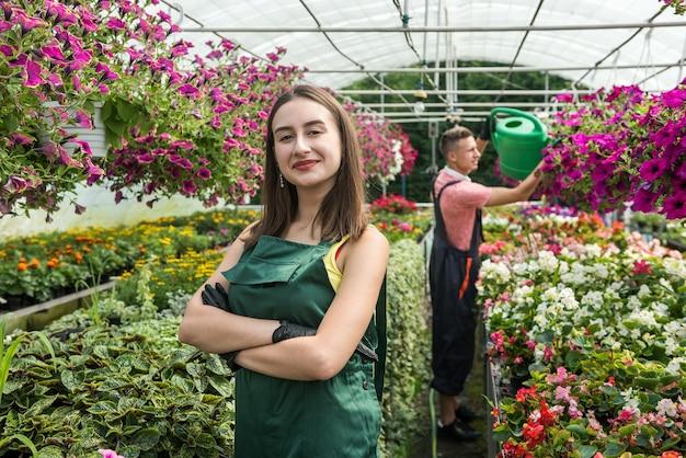 温室の若い労働者は花を食べます。植物の世話の概念