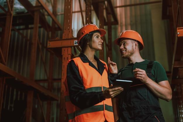 Молодые рабочие в касках разговаривают на складе