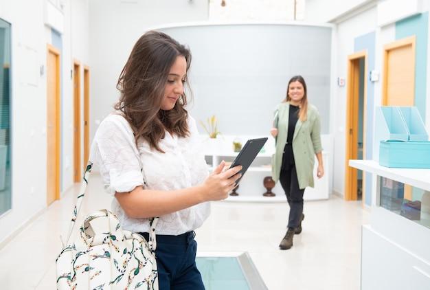 Молодые работники в своем офисе улыбаются