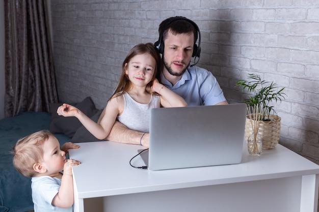 若い働く父親は彼の子供たちと猫を自宅でベビーシッターしながら、ヘッドフォン付きのラップトップで働いています。