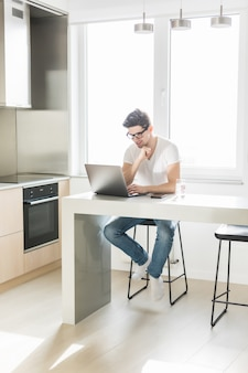 Young working man in kitchen using laptop smiling
